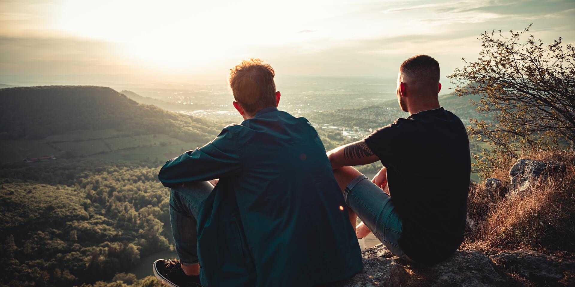 Zwei junge Männer sitzen an einem Aussichtspunkt und blicken auf ein Tal