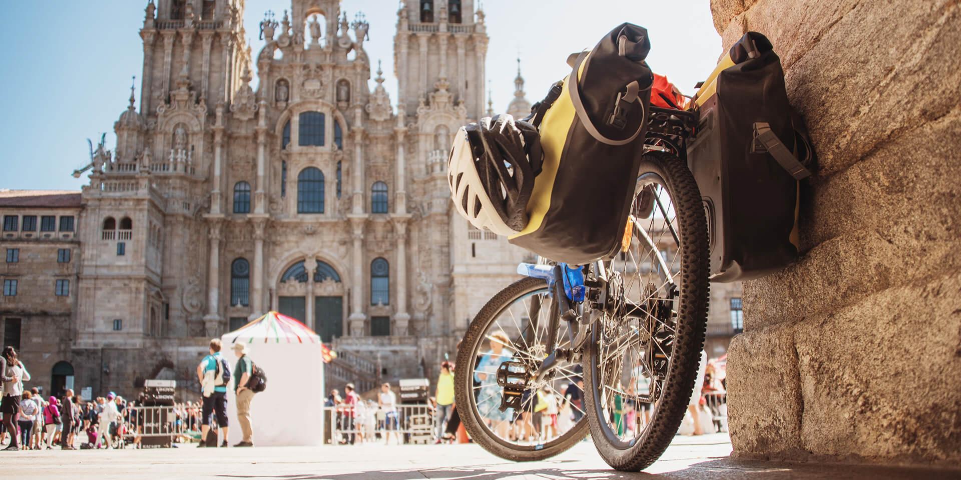 Ein Fahrrad mit gepackten Satteltaschen steht vor der Kathedrale von Santiago de Compostela